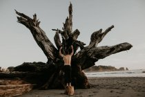 Back view of shirtless man leaning on big fallen tree trunk on beach. — Stock Photo