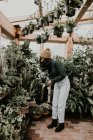 Side view of girl looking at plants at hothouse — Stock Photo