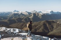Side view of man in outerwear on background of snowy mountains — Stock Photo