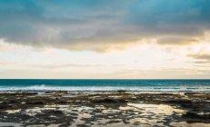 Découvre à nuageux ciel coucher de soleil sur mer — Photo de stock