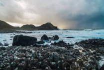 Vue panoramique de pierres et de collines au bord de mer — Photo de stock
