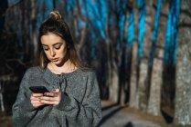 Retrato de mujer en Jersey con teléfono en callejón del parque - foto de stock