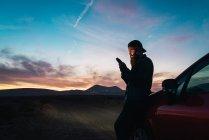 Seitenansicht eines Touristen, der sich in der Abenddämmerung ans Auto lehnt und auf dem Land mit dem Smartphone surft — Stockfoto