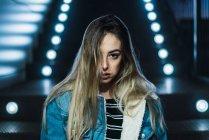Retrato de jovem olhando seriamente câmera no fundo das escadas com luz de neon. — Fotografia de Stock