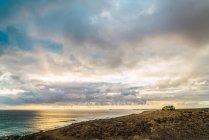 Vue panoramique mer nuageuse et van garé au lointain — Photo de stock