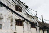 Опори ліній на фоні старих сірих бетонної шорсткою будівель у місті. — стокове фото