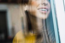 View through glass of smiling woman standing and smiling at window at home. — Stock Photo