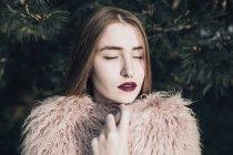 Sensuelle fille élégante avec des lèvres lumineuses posant par branches de sapin avec les yeux fermés — Photo de stock