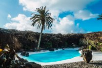 Exterior view of blue pool and palm tree on sunny day — Stock Photo