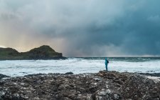 Distant view of tourist standing on rocky coast and looking at ocean — Stock Photo