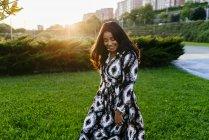 Портрет веселий жінка в сукні, ходьба на сонячній галявині в парку — стокове фото