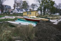 Row of small boats placed on shore at small houses in countryside. — Stock Photo