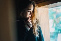 Side view of young woman cuddling in sweater and looking away in window. — Stock Photo