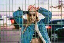 Соблазнительная молодая блондинка позирует за чистым забором — стоковое фото