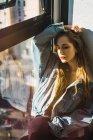 Ragazza elegante posa vicino alla finestra alla luce del sole — Foto stock