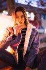 Ritratto di donna in giacca di jeans che guarda la macchina fotografica con provocazione e seduta vicino alla luce della lampada sulla strada — Foto stock