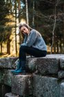 Портрет молодой женщины, опирающейся на руку и сидящей на каменной стене в осеннем лесу — стоковое фото