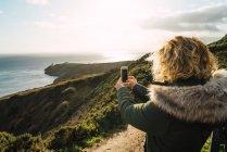 Rückansicht des touristischen Frau stehend auf küstennahen Klippen und Aufnahmen des Meeres mit smartphone — Stockfoto