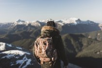 Rear view of man in outerwear admiring snowy mountains — Stock Photo