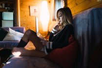 Side view of sensual woman in sweater watching laptop while sitting on couch in house. — Stock Photo