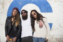 Grupo de amigos, apoyado en la pared y posando en la cámara - foto de stock