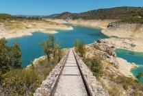Vista a pequena ferrovia liderando a azul lago nas montanhas. — Fotografia de Stock