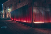Illuminated with red metal fence on street at night. — Stock Photo