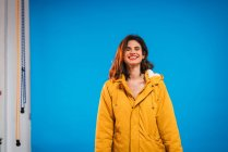 Cheerful woman in yellow jacket against blue backdrop — Stock Photo