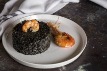 Still life of black rice with prawns on white plate on old table. — Stock Photo