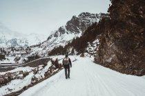 Rear view of backpacker walking on snowy mountain road — Stock Photo
