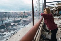 Side view of thoughtful young woman leaning on handrail and looking away at window of grungy building. — Stock Photo