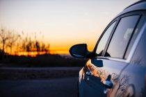 Ernte geparkten Auto über Sonnenuntergang Himmel — Stockfoto
