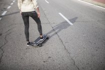 Low section of girl riding longboard on urban asphalt road — Stock Photo