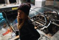 Молодая женщина в шляпе позирует в выветривания здания и глядя на камеру — стоковое фото