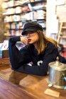 Jeune jolie femme assise à table en bibliothéconomie et en regardant la caméra — Photo de stock