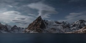 Panorama of lake amid snowy mountains in evening dusk — Stock Photo