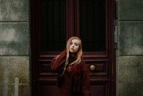 Femme blonde en pull posant à porte — Photo de stock