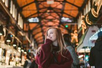 Cheerful young woman standing at cases on funfair and looking away — Stock Photo