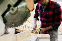 Cropped carpenter taking measure in piece of wood at workbench — Stock Photo