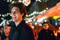 Fröhlicher Mensch lächelnd auf Stadtstraße Abend — Stockfoto