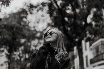 Красивая женщина в солнечных очках ходит по улице — стоковое фото