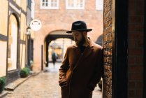 Homme élégant dans des vêtements vintage, s'appuyant sur le mur de l'arche — Photo de stock