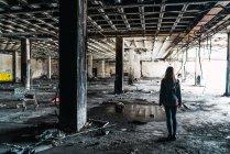 Vue arrière de jolie femme debout au milieu d'une pièce abandonnée altérée . — Photo de stock