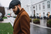Side view of bearded man in vintage cap and coat posing at street scene — Stock Photo