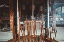 Bastoncini di incenso che bruciano con fumo al tempio orientale — Foto stock