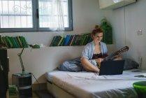 Femme rousse avec guitare navigation ordinateur portable sur le lit — Photo de stock