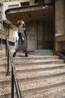 Trendige Mädchen posiert auf Treppen und Wegsehen — Stockfoto