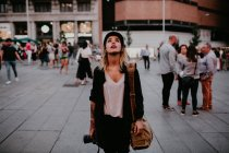 Mulher com a câmera no quadrado e olhando para cima — Fotografia de Stock