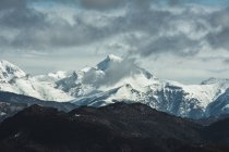 Breathtaking panorama of mountains range covered with snow under cloudy sky. — Stock Photo