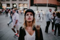 Portrait of woman in black cap standing at street and looking up — Stock Photo